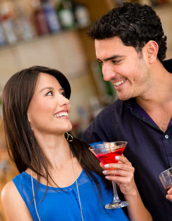 Couple having a drink at the bar and smiling photo