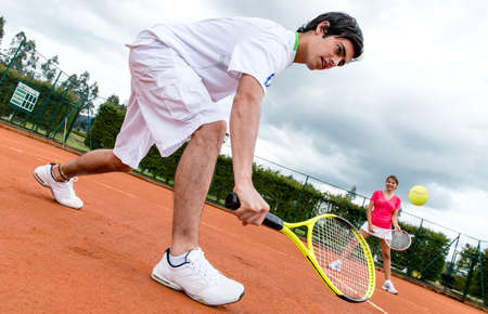 Couple playing doubles in tennis at a clay court photo