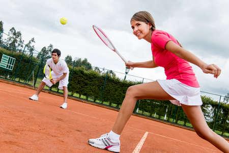 jugando tenis: Mujer que juegan dobles en el tenis en una cancha de arcilla