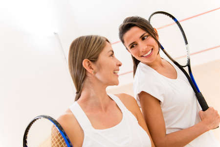 squash: Female squash players at the court holding rackets