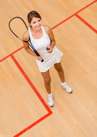 Happy woman playing squash at the court photo