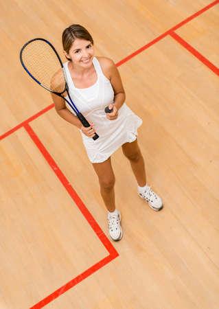 racket sport: Mujer feliz jugando al squash en la corte