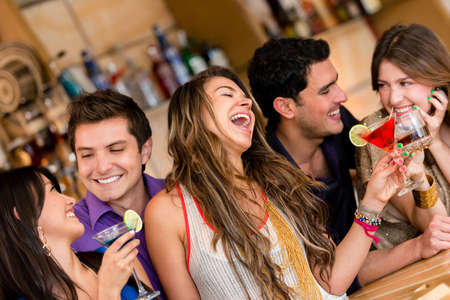 alcoholic drinks: Happy group of friends at the bar having drinks