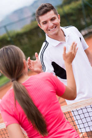 Happy tennis trainer giving high five to a woman photo