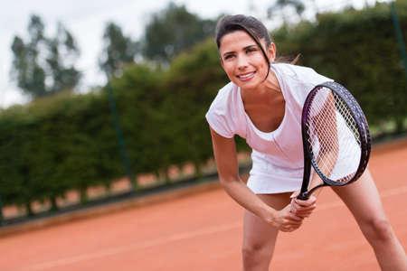 jugando tenis: Mujer que juega a tenis en la pista y con raqueta