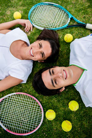 Couple of tennis players lying in the floor with rackets and balls photo
