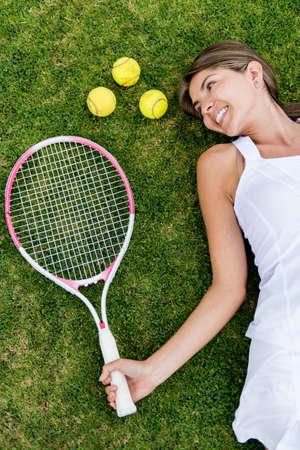 tennis: Joueur de tennis f�minin allong� sur le sol avec une raquette et des balles