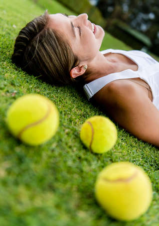lawn tennis: Female tennis player relaxing outdoors lying on the lawn
