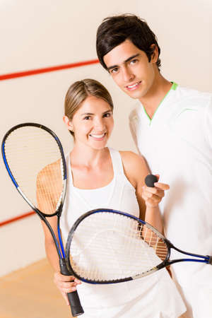 squash: Couple of squash players at the court holding rackets Stock Photo
