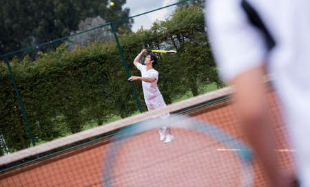 Male player serving at a tennis match photo