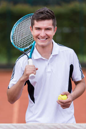 Happy male tennis player smiling at the court photo