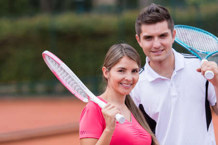 Happy couple playing tennis outdoors and smiling photo