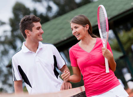 fit couple: Couple of players at the tennis court looking happy Stock Photo