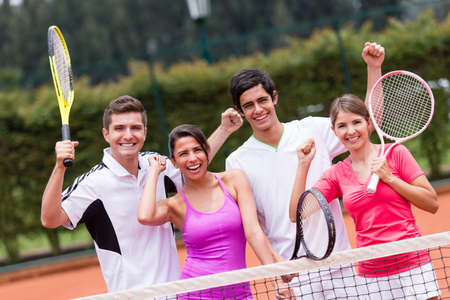 Excited group of tennis players with arms up photo