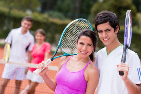 Happy tennis couple playing doubles at the court photo