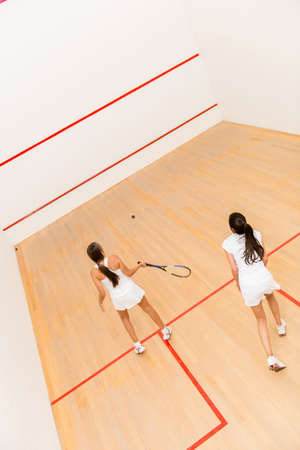 Women at the court playing a match of squash photo
