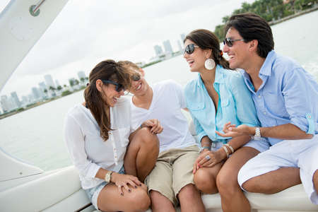 Happy group of friends having fun sailing on a boat photo