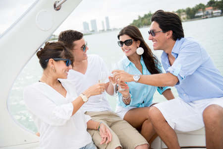 yachts: Happy group of people on a boat making a toast