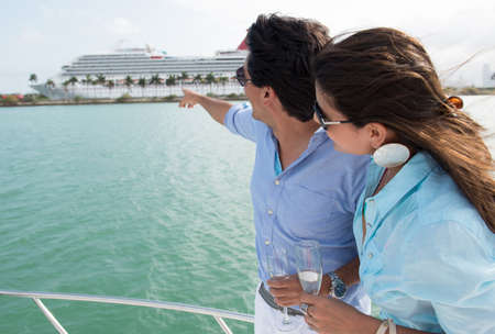 Summer couple on the boat pointing at a cruise photo