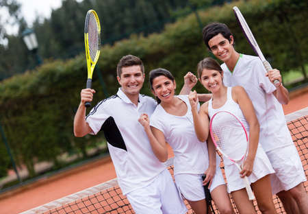 Happy group of tennis players with arms up at the court Stock Photo - 19622377
