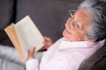 Old woman reading a book relaxing at home photo