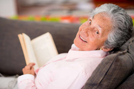 senior at home: Senior woman reading a book at home enjoying her retirement Stock Photo