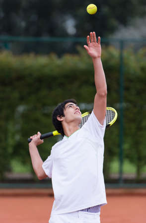 male tennis players: Man serving at a tennis match - outdoors Stock Photo