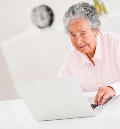 Senior woman using a laptop computer at home photo