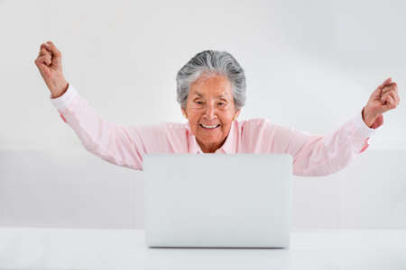 woman arms up: Elder woman celebrating her online success with arms up Stock Photo