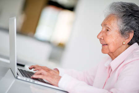 Elder woman using a computer and looking very happy photo