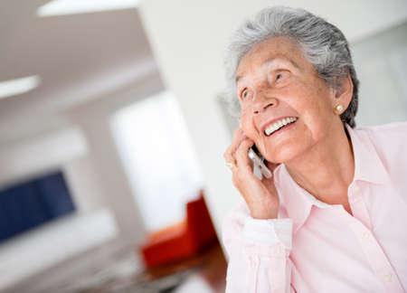hablando por celular: Mujer mayor feliz que habla en el teléfono