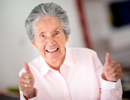 Portrait of a happy senior woman with thumbs up photo