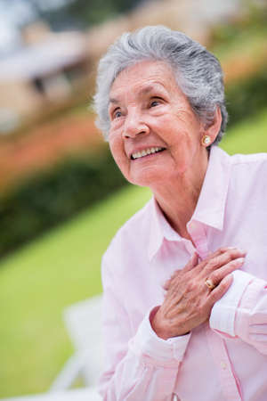 Sweet elder woman with hands on chest looking happy - outdoors photo