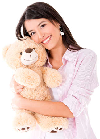 Sweet woman hugging a teddy bear and smiling - isolated over white photo