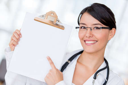 Happy female doctor pointing at the hospital photo