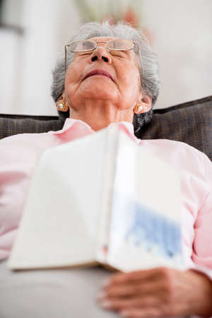 Elder woman falling asleep while reading a book photo