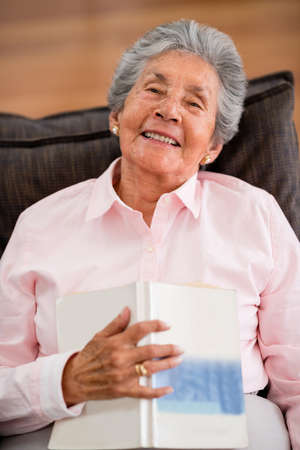 Lovely senior woman reading a book at home photo