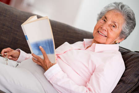 Elder woman reading a book relaxing at home Stock Photo - 19721219