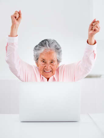 Happy elder woman with a laptop and arms up Stock Photo - 19721196