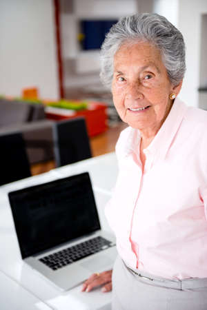 Happy senior woman at home with a laptop Stock Photo - 19721184