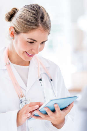 Female doctor using app on a tablet computer Stock Photo - 19721171