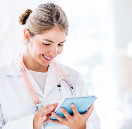 Female doctor using a tablet computer and smiling Stock Photo - 19721207