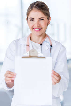 Happy female doctor holding prescription at the hospital photo