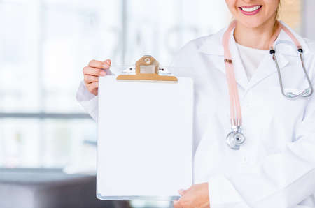 Doctor showing a clipboard with white space for your text Stock Photo - 19721204