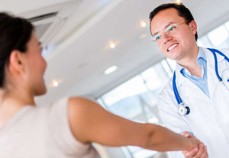 Doctor greeting patient at the hospital with a handshake photo