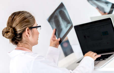 Doctor working at the hospital on a laptop and holding x-ray Stock Photo - 19721160