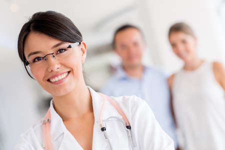 patients: Female doctor at the hospital with patients at the background