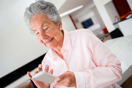 Happy senior woman using app on a cell phone photo