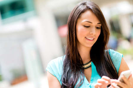 mobile apps: Woman sending a text message on her cell phone Stock Photo