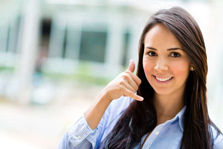 call: Business woman making a call me sign and smiling